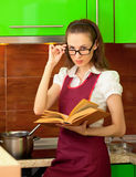 Girl reading a cookbook on kitchen Royalty Free Stock Images