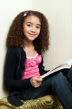 Girl reading in corner looking at camera Royalty Free Stock Photography