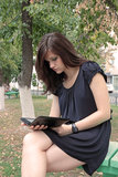 Girl reading e-book. In the park Stock Image
