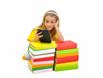 Girl reading e-book among books. Girl reading e-book among colorful books isolated on white background Stock Image