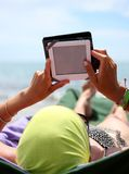 Girl reading an ebook lying on sun loungers on the beach Stock Images