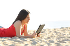 Girl reading an ebook or tablet on the beach Stock Image