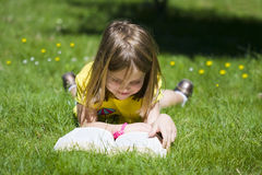 Girl reading in the field Royalty Free Stock Photo