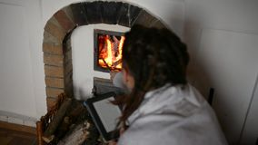 Girl reading by the fire stock video