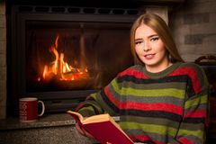 Girl reading by the fireplace sitting on the floor royalty free stock image