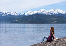 Girl reading on a fjord coast Royalty Free Stock Photos