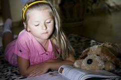 Girl reading on floor Royalty Free Stock Photography