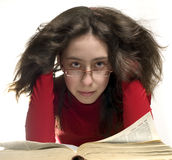 Girl with reading glasses. Girl in red cloth with big old book. Here hair is curl.  She rested his head with his hands. She have a reading glasses Royalty Free Stock Photos