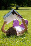 Girl reading in the grass Royalty Free Stock Photos