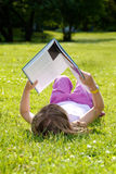 Girl reading in the grass Royalty Free Stock Photography