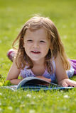 Girl reading in the grass Stock Images