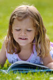 Girl reading in the grass Stock Photos