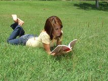 Girl reading on the grass Royalty Free Stock Photography