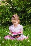 Girl is  reading on the grass Royalty Free Stock Photo