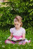 Girl is  reading on the grass Stock Photos