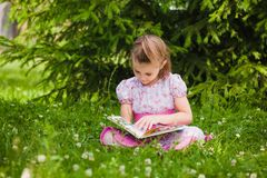 Girl is  reading on the grass Stock Photography