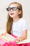 Girl reading. Happy little girl is reading a book while wearing glasses indoors Royalty Free Stock Photos