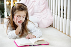 Girl reading homework. Young girl lying on the floor reading royalty free stock images