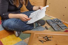 Girl reading instructions to assemble furniture. Closeup of girl with tools reading the instructions to assemble a new furniture for home stock photos