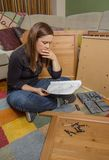 Girl reading instructions to assemble furniture Royalty Free Stock Images