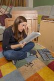 Girl reading instructions to assemble furniture Royalty Free Stock Photos