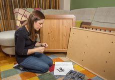 Girl reading instructions to assemble furniture Stock Image
