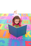 Girl reading kids book lying on alphabet floor mat Stock Images