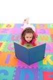 Girl reading kids book lying on alphabet floor mat. Young girl reading book on alphabet floor mat. Isolated on white Stock Images