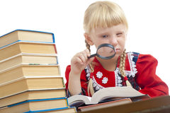 Girl reading with loupe Stock Image
