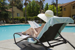 Girl is reading a magazin. Girl in a summer heat is reading a magazin by the swimming pool Royalty Free Stock Image