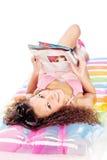 Girl reading magazine on air mattress. Pretty curl girl reading newspaper on air mattress, isolated on white Stock Photo