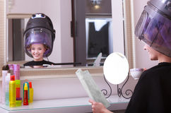 Girl reading magazine drinking coffee. Hairdryer in hair beauty salon Royalty Free Stock Image