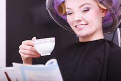 Girl reading magazine drinking coffee. Hairdryer in hair beauty salon Royalty Free Stock Photography