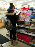 Girl reading magazine in supermarket Stock Image