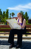 Girl is reading the map. Stock Photo