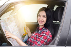 Girl reading a map in car Stock Photo