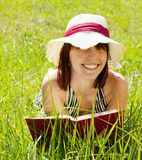 Girl reading in meadow Stock Photo