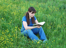 Girl reading at the meadow Stock Images