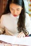 Girl reading menu at Chinese restaurant. Asian girl reading menu at Chinese restaurant Royalty Free Stock Photos