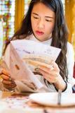Girl reading menu at Chinese restaurant. Asian girl reading menu at Chinese restaurant Royalty Free Stock Photography