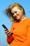 Girl reading a message. On her cellular phone against blue sky Stock Photography