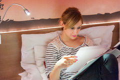 Girl Reading Notebook in Bed Stock Image