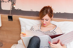 Girl Reading Notebook in Bed Stock Photos