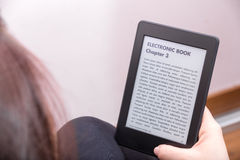 Girl is reading a novel with an e-book reader Royalty Free Stock Photography