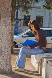 Girl reading outdoor. Portrait of a student girl reading papers outdoor in an urban park Stock Photos