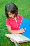 Girl reading outdoors Stock Image