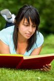 Girl reading outdoors Stock Photos