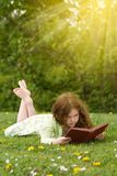 Girl Reading Outdoors. Young girl reading a book outdoors in summertime Royalty Free Stock Images