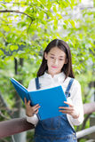 Girl reading outdoors. Pretty girl reading under a tree, asian girl Stock Photography