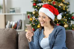Girl reading phone messages in christmas at home. Girl reading phone messages in christmas sitting on a couch in the living room at home royalty free stock image